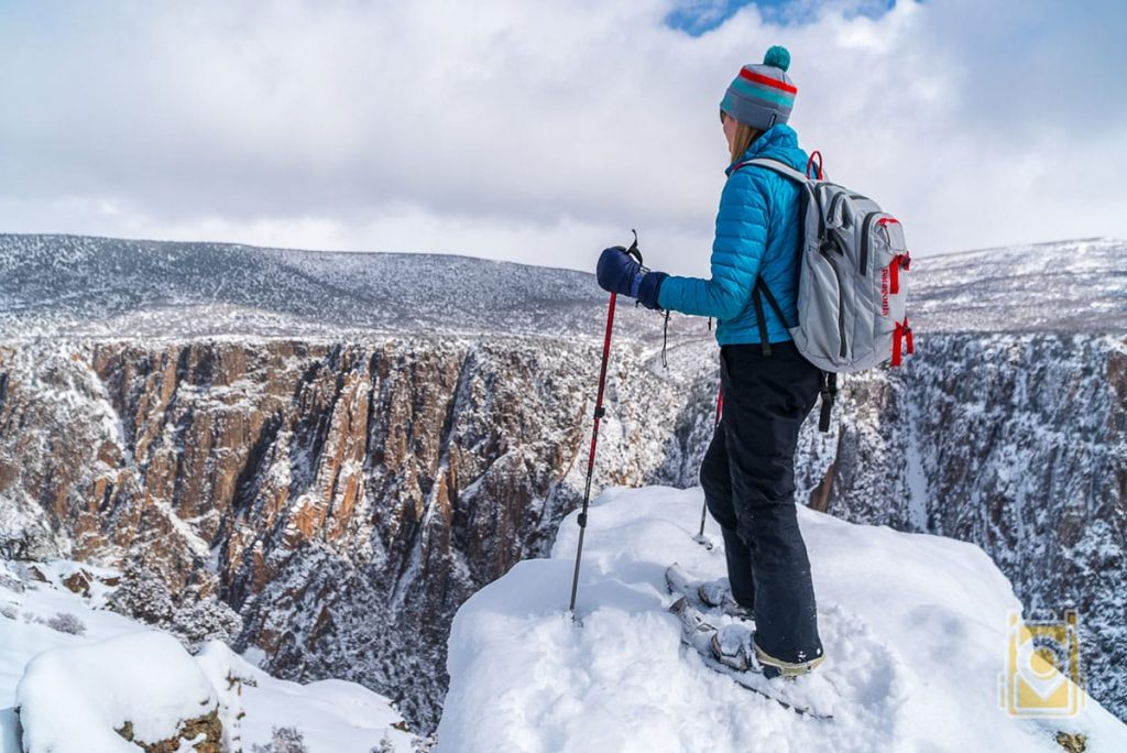 Tiffany looking out over the Black Canyon of the Gunnison National Park during a snowshoe trip.
