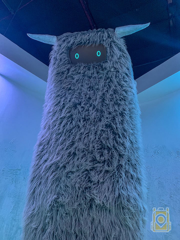 A large, furry, horned beast gazes down at us in one of the portals at Meow Wolf, Santa Fe.