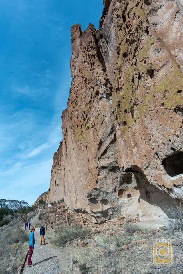 How to Spend a Day in Bandelier: Tiffany examines some petroglyphs on a cliff wall in Bandelier National Monument